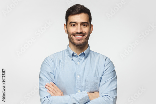 Smiling businessman in blue shirt isolated on gray background