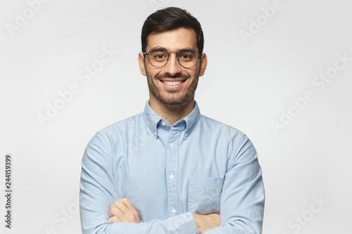 Portrait of young male teacher smiling, wearing blue shirt, isolated on gray bac Fototapeta