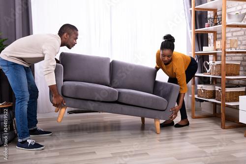 Fotografie, Obraz  Couple Lifting Sofa In Living Room