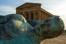 Close-up Of Icarus Bronze Statue With Temple Of Concordia At Valle Dei Templi (Valley Of The Temples), UNESCO World Heritage Site, Agrigento, Sicily, Italy