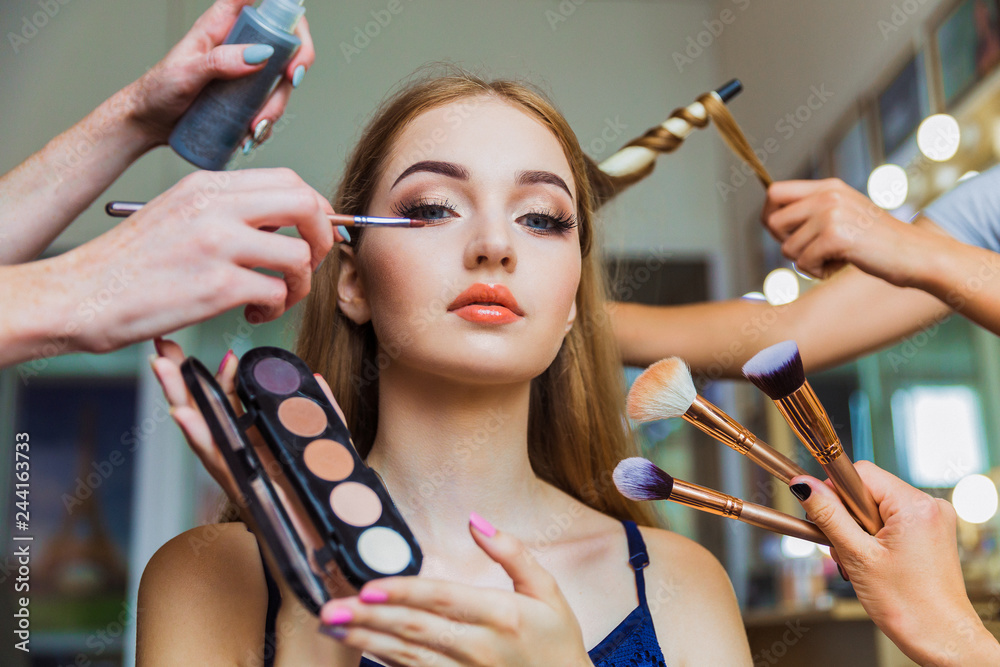 Fototapeta Portrait of the charming young woman who is sitting indoors and makeup artist doing makeup her and hairdresser doing the hairdo her