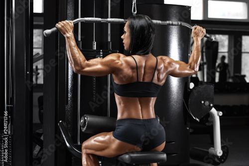 Fototapeta Muscular woman working out in gym doing exercise for back. Strong fitness girl, muscles back obraz