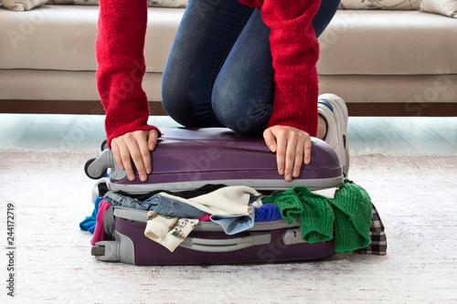 Fototapeta Young woman standing on her knees on overfilled suitcase, trying to close it. obraz