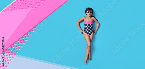 Obraz Fashion child summer. Little girl kid in swimsuit lay view top. Concept beach vacation. Blank, banner, copy space for ,advertising. Isolated pink, blue color background like sea water in studio. - fototapety do salonu