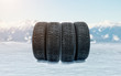 Four car winter tires on an icy surface as a symbol of safe driving during snowy season