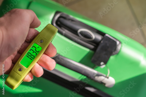 Photo Wiegen des Koffers mit einer Kofferwaage
