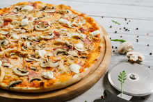 Tasty Pizza With Mozzarella, Hum, Chicken Fillet, And Champingnons On The White Wooden Background