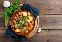 Meat Stewed With Potatoes, Carrots And Spices In Ceramic Pot On Wooden Background .