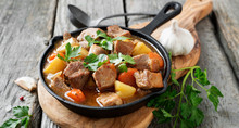 Meat Stewed With Potatoes, Carrots And Spices In Iron Pan On Wooden Background .