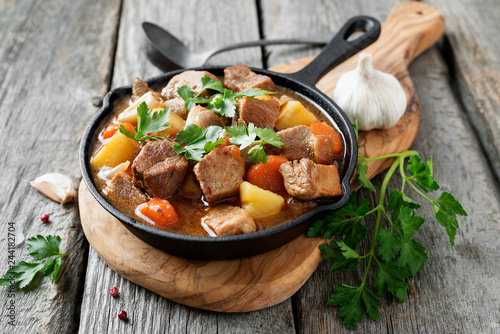Meat stewed with potatoes, carrots and spices in iron pan on wooden background Canvas Print
