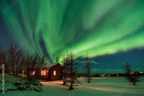 Valokuva  Aurora over cottage in Iceland