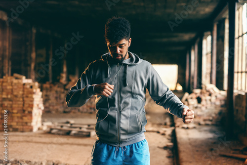 Fototapeta Portrait of african american guy in sportswear working out in old brick factory. Healthy lifestyle concept. obraz na płótnie