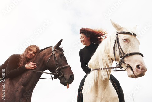 Two young pretty girls riding a horses on a field Fotobehang