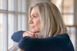 Leinwanddruck Bild - Attractive blond woman watching through a window