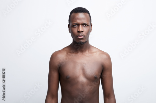 Valokuva  Close up shot of serious dark skinned male with scared and anxious emotion on face, feels astonishment as sees something unexpected, posing shirtless, isolated over white background