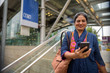 Indian woman using mobile phone outside of train station in Bangkok