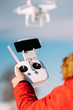 close up details of drone remote control and white drone in blue sky. Man operating drone, pilotage details