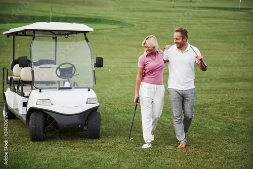 Deurstickers Golf Two golfers, a woman and a man, go together to the next hole. A student goes with her personal trainer and is pleased with her success in sports