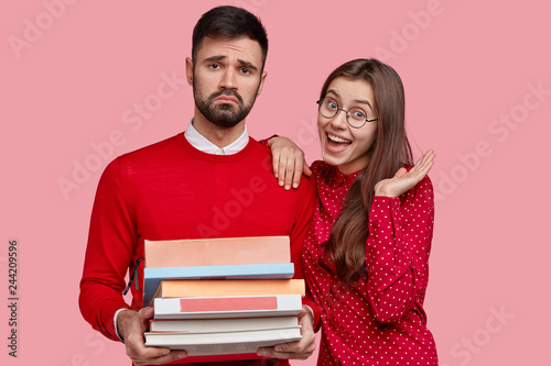 Fotografía  Dissatisfied man with upset look, carries pile of books, tired of studying, happy Caucasian girlfriend expresses good emotions, stand closely, isolated over pink background
