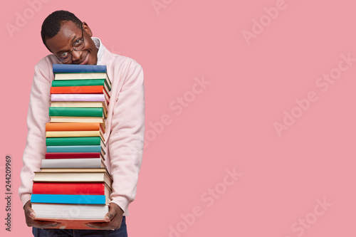 Fotografía  Pleased dark skinned hipster student leans on pile of heavy books, wears casual sweater, round spectacles, isolated over pink background with free space for your advertising text