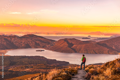 Poster Diepbruine Hiking wanderlust adventure man hiker alone looking at sunset nature landscape of mountains and lakes during summer. Travel outdoors freedom lifestye.