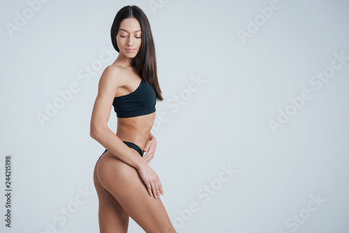 Fototapeta Portrait of brunette girl in underwear standing in the studio with white background obraz na płótnie