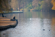 Two Fishermen On The Banks Of A River Try To Catch Fish In The Early Morning Light During Autumn Fall