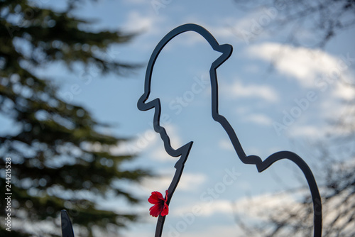 Fényképezés cut out figure of soldier wearing a poppy with blue sky shining through as a sym
