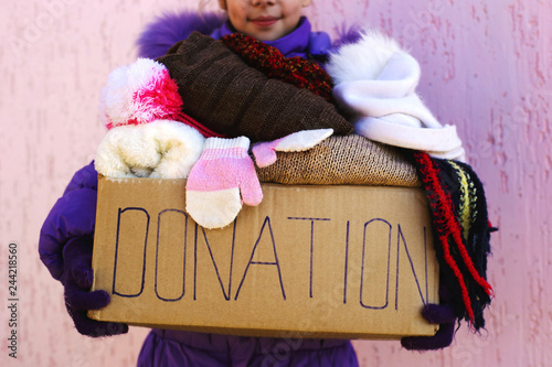 Fényképezés Girl holding donation box with warm winter clothes.