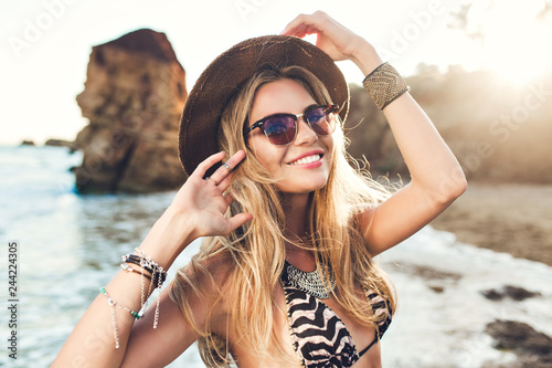 Fotografia  Portrait of attractive blonde girl with long hair posing on rocky beach