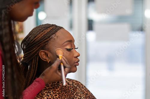 Fényképezés A black make up artist applying blush to a black model with pigtails