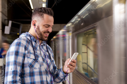 Student traveler waiting for train listening to music on a smartphone. Concept of leisure, communication, social media.