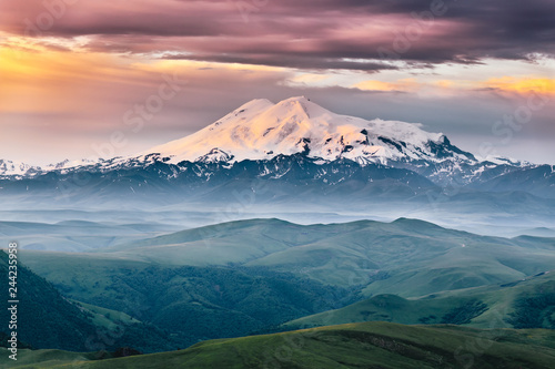 Poster Campagne Beautiful view of Elbrus mount in the morning at sunrise with a dramatic cloudy sky and foggy green highland meadows. Summer mountain landscape. North Caucasus, Karachay-Cherkess Republic, Russia
