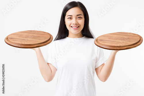 Wooden pan. Young asian woman in summer tshirt holding empty pizza tray isolated on white background. Copy space and mock up. Blank template t shirt background.