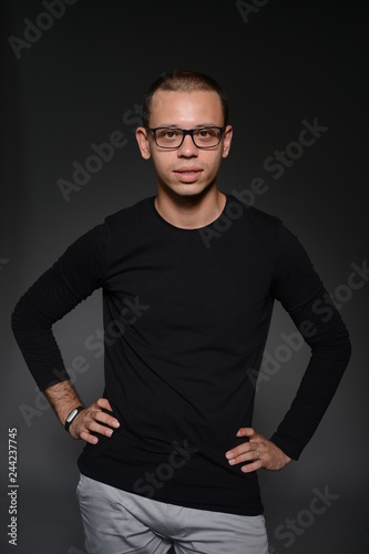 Fototapety, obrazy: a man in a black jacket shows emotions in the Studio on a black background