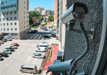 External Surveillance Cameras Are Mounted On Building Wall, Viewing Parking Lot