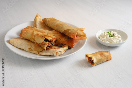 filo or yufka dough rolls stuffed with a spicy meat filling and cheese curd on a white painted table, copy space