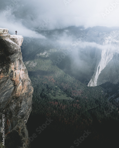 Man standing at edge of cliff over Yosemite Valley, California, USA Canvas Print