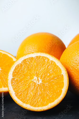 Photo Stands Slices of fruit Orange, ripe citrus fruits and round slice on a black, textured table and white background