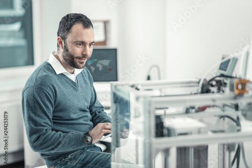 Fotografía  Delighted smart man sitting near the 3d printer