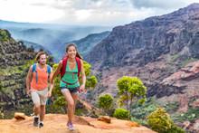 Young Happy Hikers People Walking On Hawaii Waimea Canyon Trail, Kauai Island, USA. Asian Woman And Man Couple Trekkng In Scenic Mountain Background. Hiking Adventure In Nature.