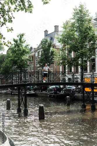 Photo man posing on the bridge in amsterdam.
