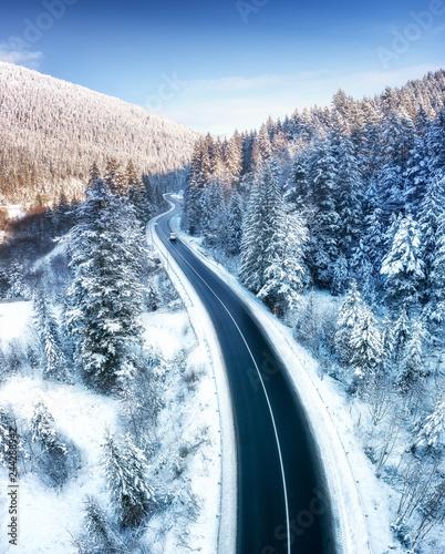 Widok z lotu ptaka na drodze i lesie w czasie zimy. Naturalny zimowy krajobraz z powietrza. Las pod śniegiem w okresie zimowym. Krajobraz z drona