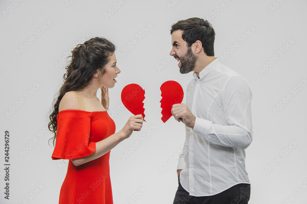 Fototapeta Portrait of an Excessive Couple. Conducting two parts of the heart paper. Isolated on a white background.