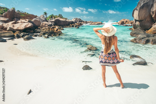 Fotografie, Obraz  A young girl standing in shallow water on La Digue island, Seychelles