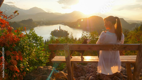 Montage in der Fensternische Camping SUN FLARE: Happy young woman and her adorable dog watching the sunset over Bled.