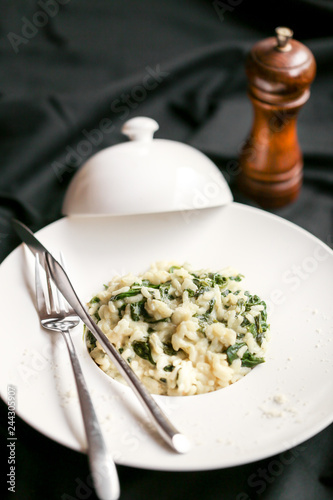 Risotto aux épinards servi sur une assiette cloche