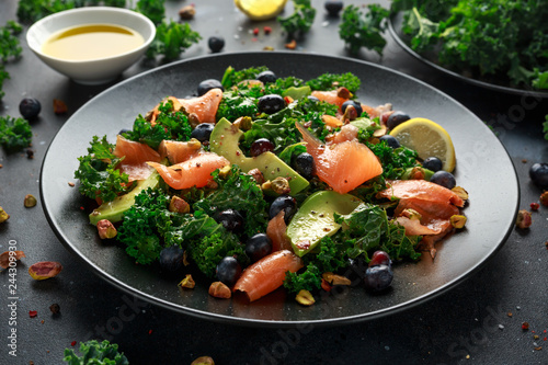 Salmon Kale super food Salad with avocado, pistachio nuts and blueberries on bla Wallpaper Mural