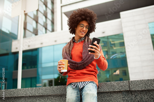 Foto  A handsome curly-haired guy of mixed race is dressed in a trendy youth-style scarf and sweater writes a message in a teleone against the background of office buildings