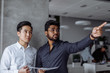 canvas print picture Mix raced couple of male business partners analyzing reports against grey wall. Indian and Chinese men in formal shirts standing in grey office boardroom, Indian man pointing aside. Marketing concept